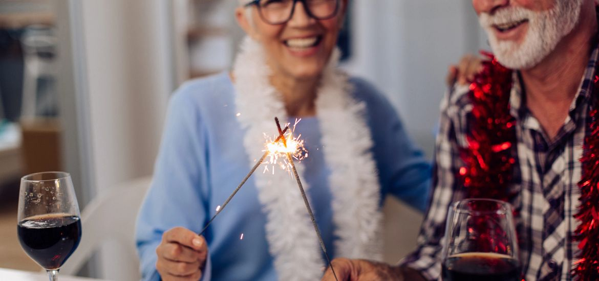 senior couple with gray hair holding sparklers