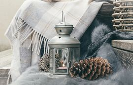 Lantern and pinecone on cozy blanket