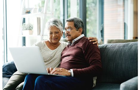 Couple Sitting in Front of Computer on Couch