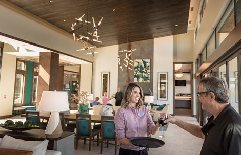 Trilogy homeowner being served a glass of wine in the clubhouse