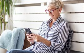 Woman with glasses sitting down and reading a text on her phone
