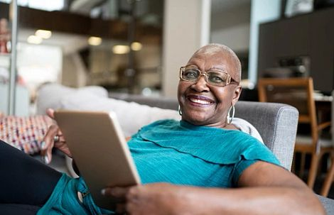 woman with glasses sitting on sofa with a tablet