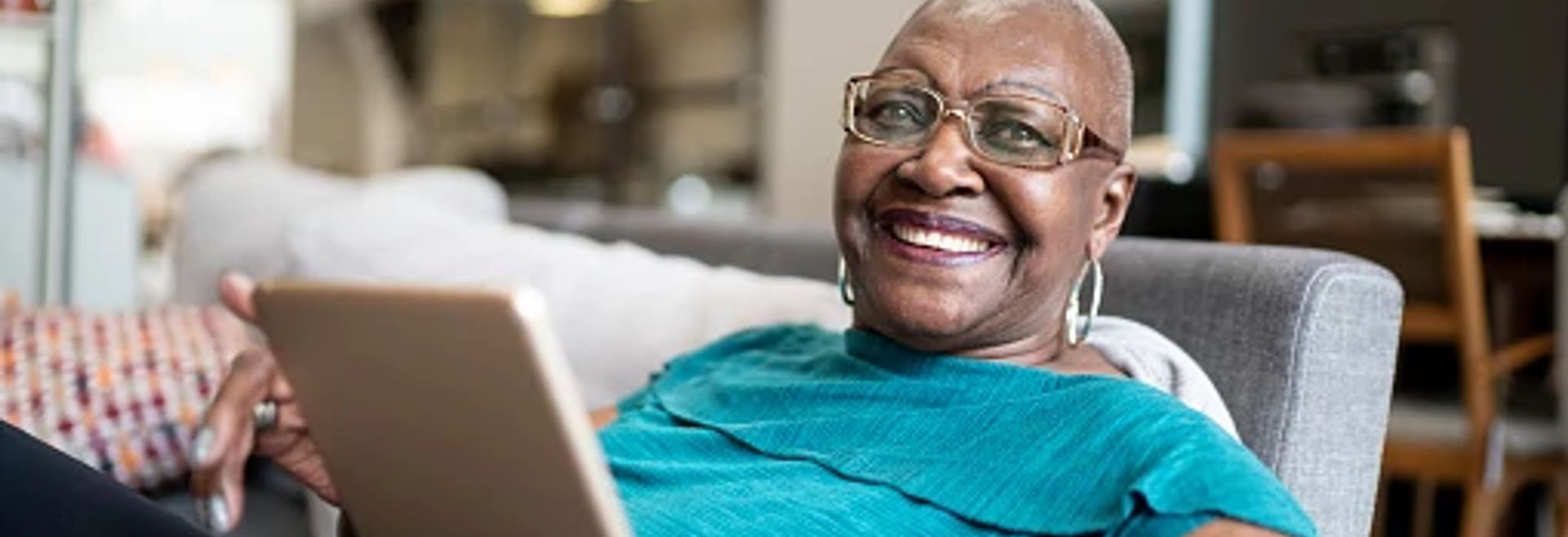 Woman sitting on a couch with a tablet