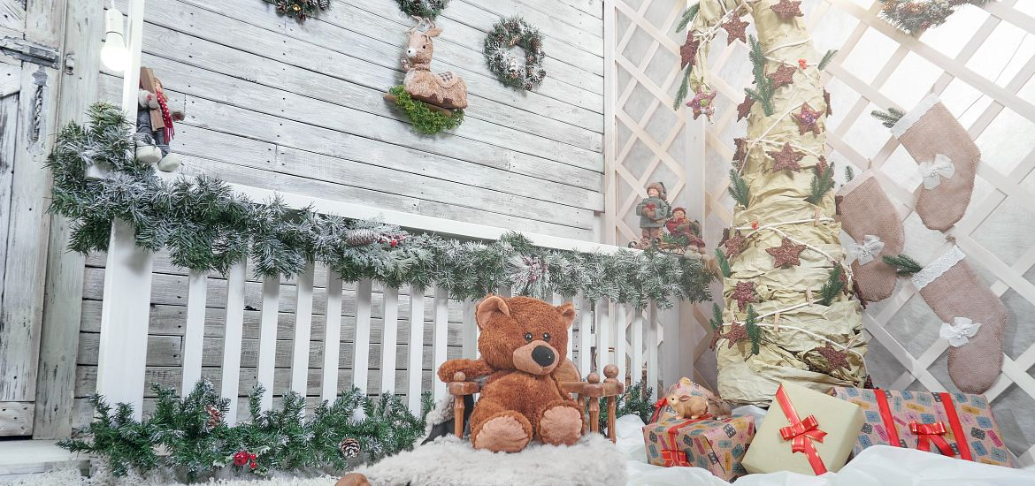 Teddy bear on sled at front of house in the snow