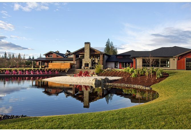 Exterior of Tehaleh Lodge with reflection pond, grass, trees, and planted flowers