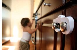baby in kitchen with cabinet locks on cabinets