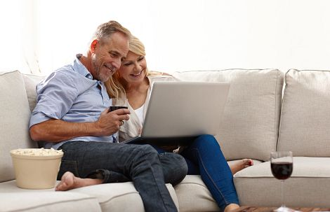 Couple on the couch at a virtual event drinking wine