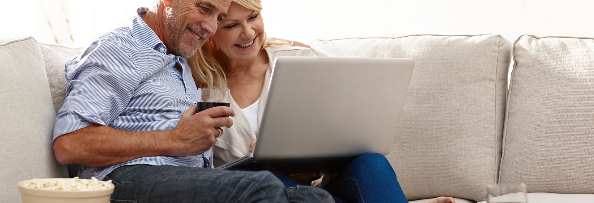 Couple sitting on the couch with their computer drinking Wine