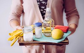 Woman in sweater holding tray of natural cleaning supplies