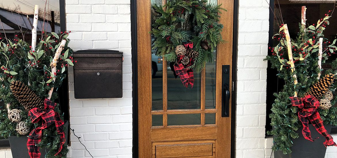 Wreath and greenery arrangements at front door of house