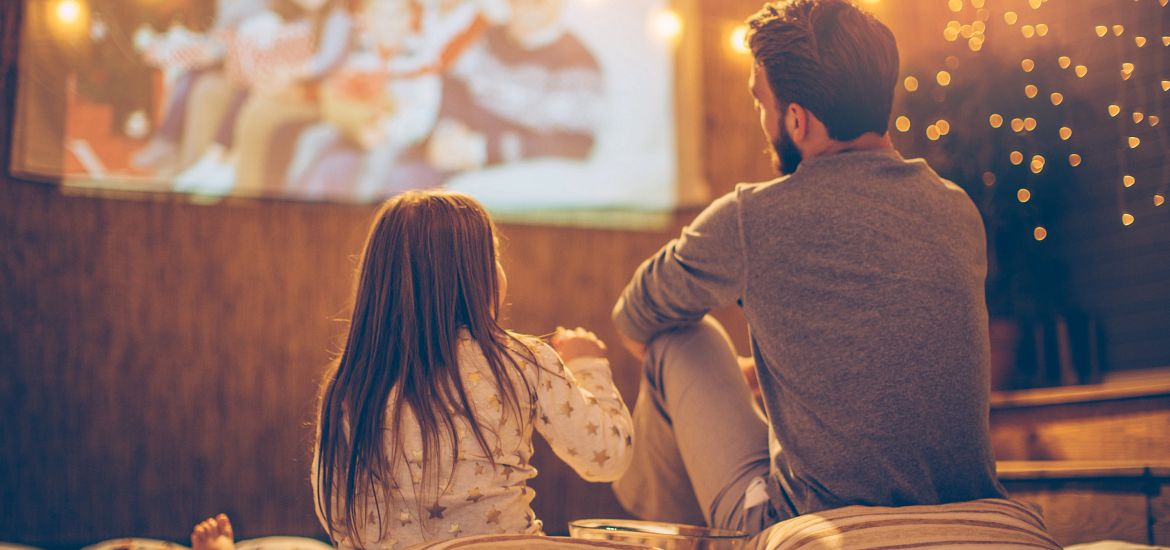 Caucasian Dad and Daughter Watching Movie Outside