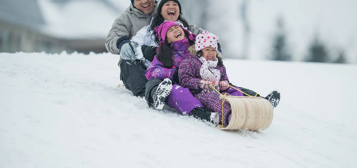 Family Sledding Colorado Snow Hill Getty Images