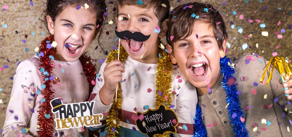 3 kids with photo props celebrating the new year