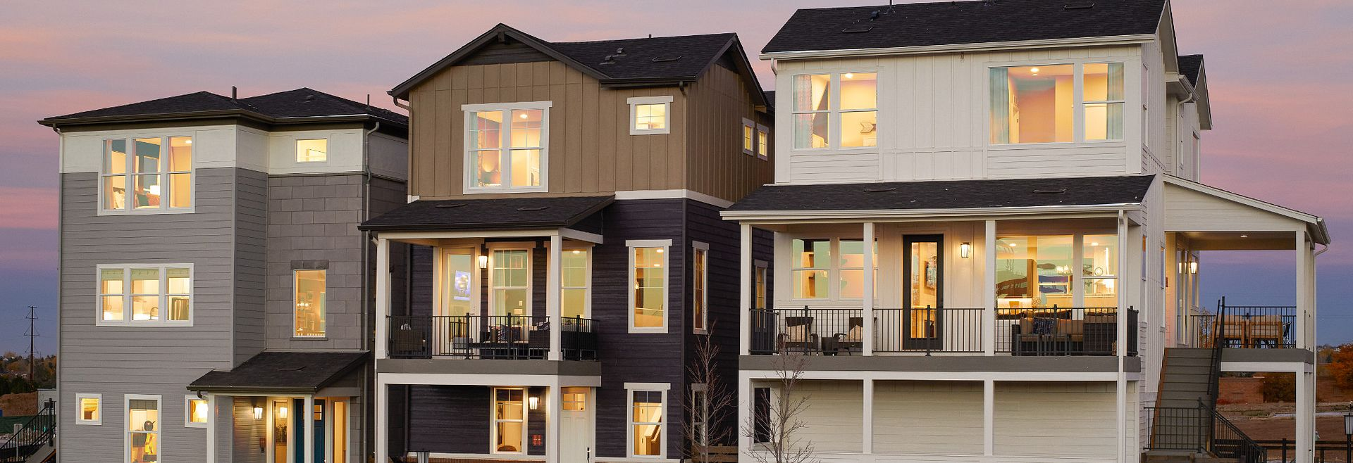 exterior of 3 model homes in evening at Crescendo Central Park in Colorado