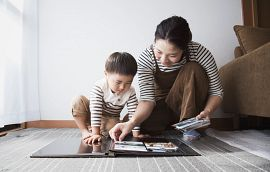 Mother and Son putting pictures in an album