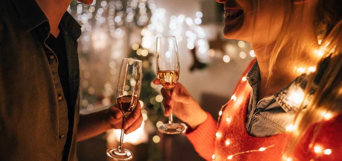 couple with holiday lights holding champagne glasses