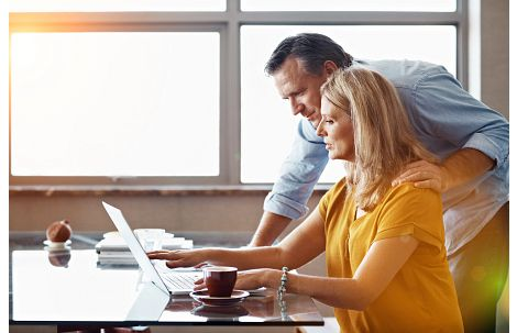 Man ad woman looking at a laptop computer on a desk