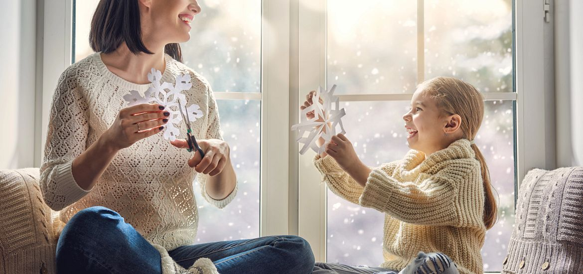 Mother Daughter Handmaking Paper Snowflakes Getty Images