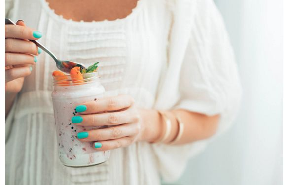 woman with a spoonful of a healthy snack in a mason jar