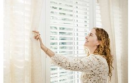 Woman Opening Curtains and Blinds to Brighten a Room