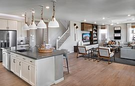 Kitchen island and living area at Ascent at Aloravita Plan 4016